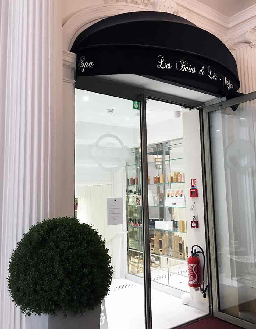 white column, black awning, shelves with beauty products behind a glass door