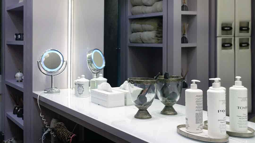 dressing room white counter with mirror and bottles of bath lotions
