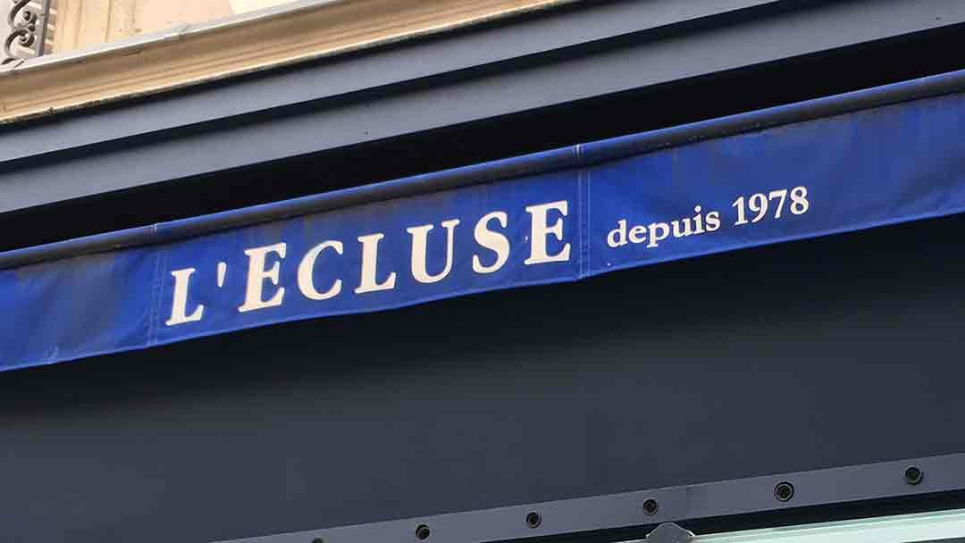 Blue awning with white letters saying L'Ecluse depuis 1978