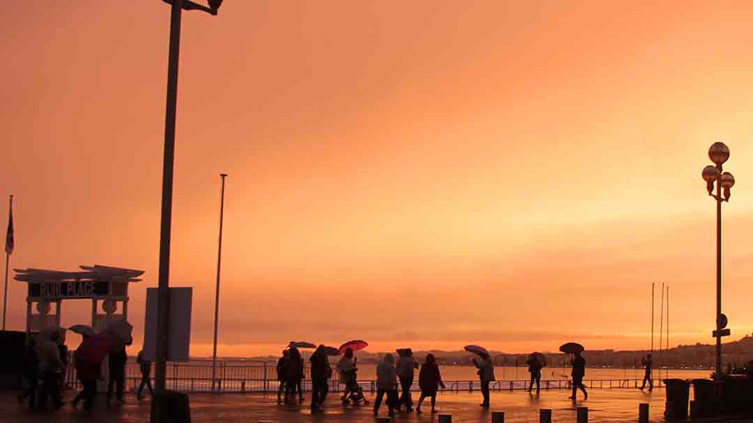 people standing on a sidewalk with an orange and yellow streaked sunset behind them