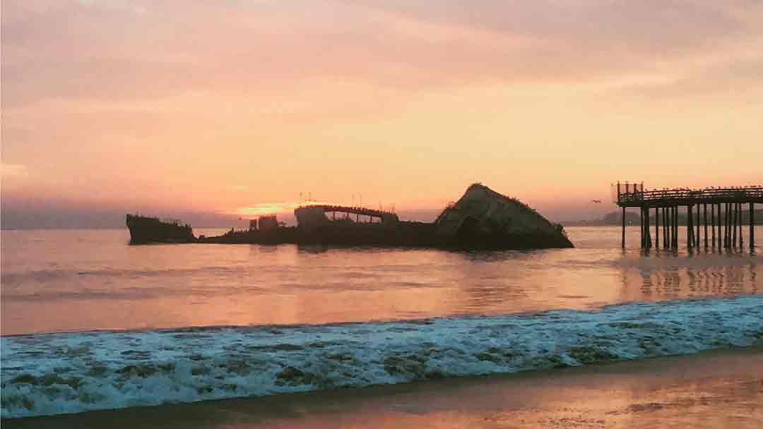 Orange setting over the ocean behind Seacliff Beach's Cement Ship