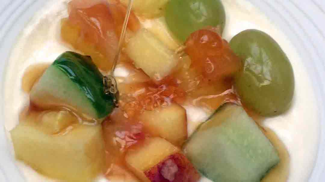 honey drizzling over creamy yogurt topped with green grapes and melon