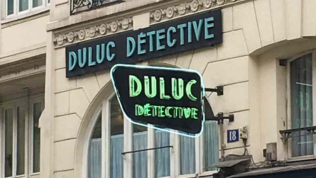 beige building with 2 neon signs, both reading Duluc Detective. One is in blue and one in green