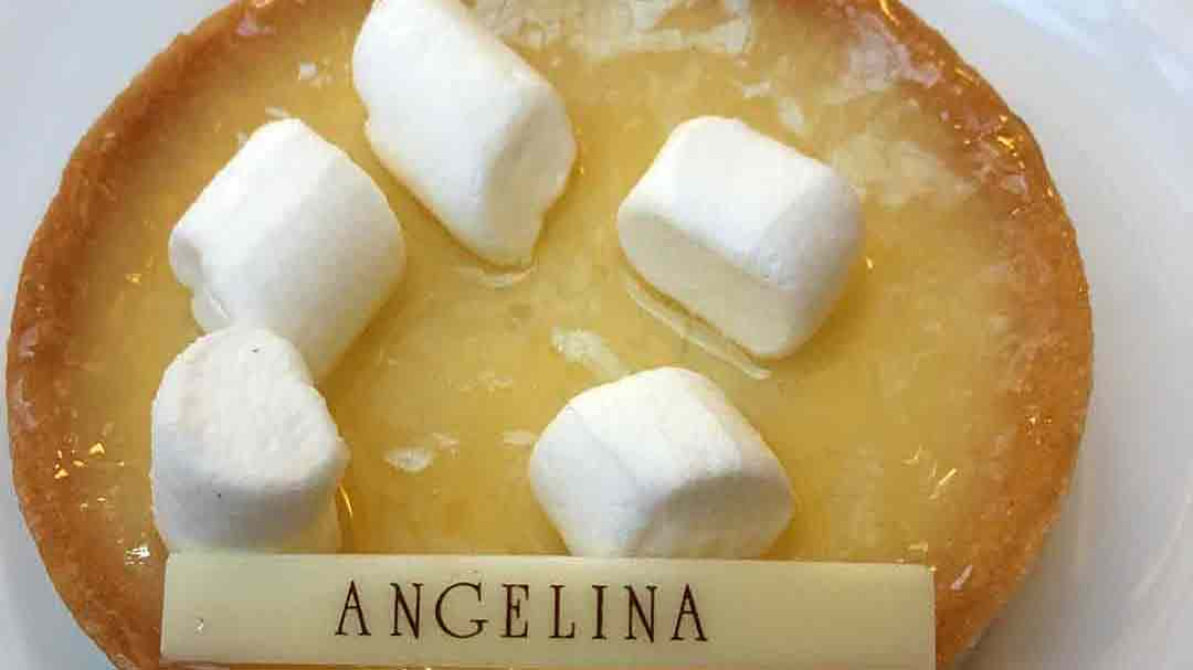Yellow creme brûlée topped with small marshmallows and a tag reading Angelina